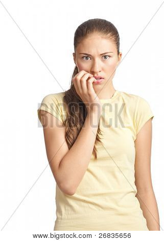 Portrait of a scared young woman biting her nails. Isolated on white background