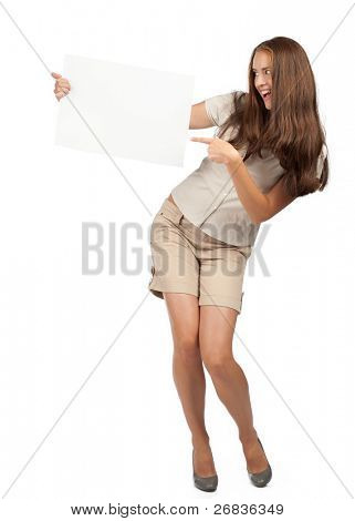 Portrait of a excited young woman holding a blank signboard and pointing, isolated on white background