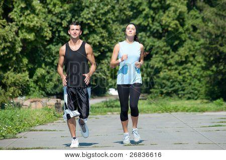 Junge Fitness paar von Mann und Frau Joggen im park