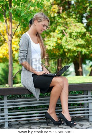 Young  business woman sitting on a park bench and using laptop outdoors