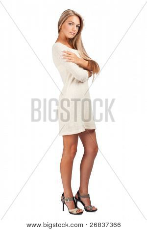 Full length portrait of young stylish woman with serious face and crossed arms, against white background