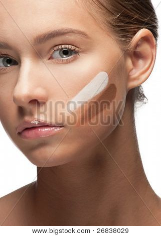 Close-up of beautiful young woman with stokes of foundation on her face