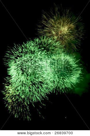 Multiple green fireworks high in the sky