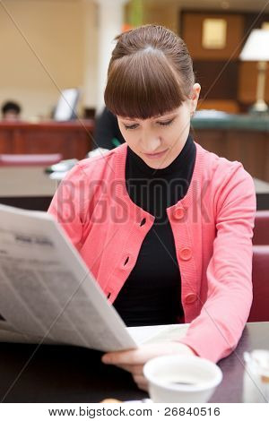 Young woman reading newspaper in hotel lobby, limited focus