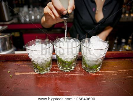 Female bartender pouring juice in glass - preparing mojito.