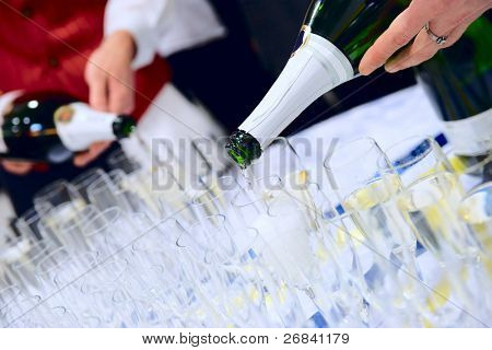 Waiter are pouring champagne  to serve large banquet table