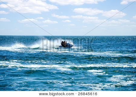 silhouette of high speed jet ski with water spray