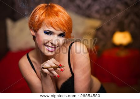 elegant woman in black bra hold cigar and smoke. retro style. Shallow focus