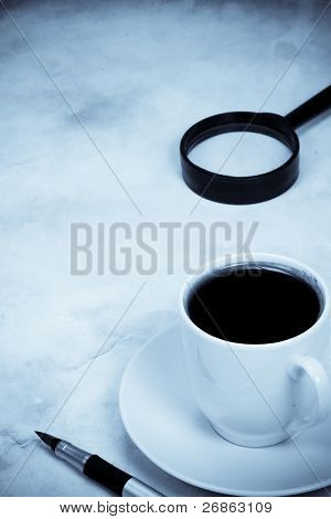 magnifying glass and coffee in blue tint