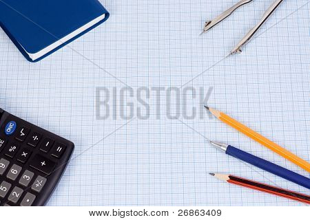 book, calculator and pens at paper