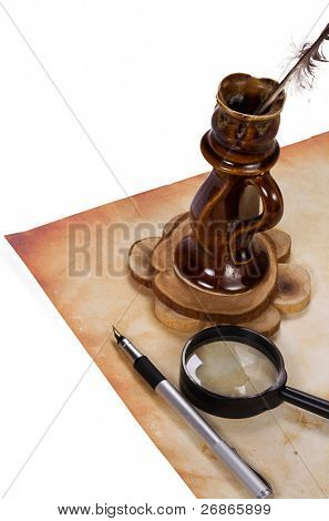 magnifier, inkpot and feather at old paper