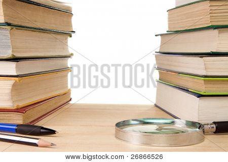 book, pen and magnifying glass isolated on white