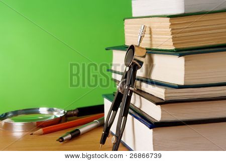 pen, ink pen, pile of books and magnifying glass on wood table