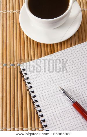 pen on notebok and cup of coffee on straw