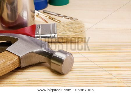 hammer, drill, paintbrush and other instruments on wood texture