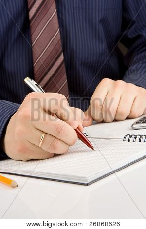 male hand writing by pen on checked notebook