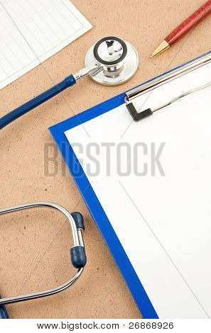 medical stethoscope with form blank on wood and pen