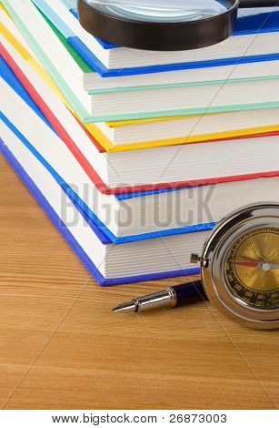 pile of books and pen on wood background