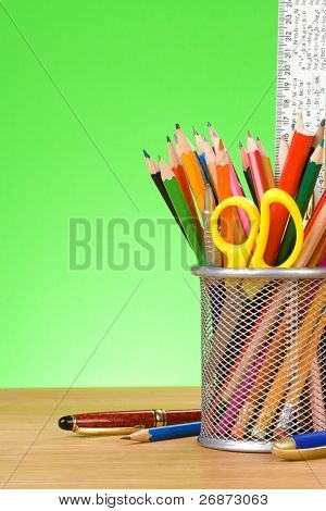 pen and pens in holder on green background
