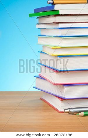 pile of books and pens on blue background