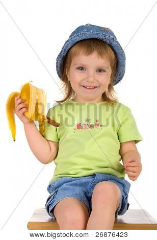 Little girl eats a banana. Studio shot