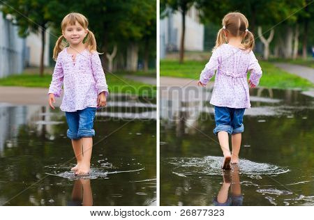 Girl to walk barefoot in a puddle splashing water in the rain