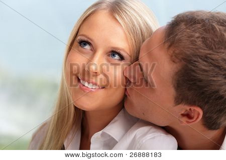 Young man kissing his girlfriend in a cheek
