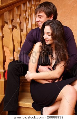 Young happy couple sitting on stairs at home