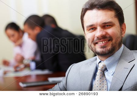 Retrato de um homem de negócios sênior feliz no escritório com sua equipe de negócios trabalhando por trás