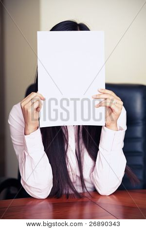 The new worker holds the white blank paper in front of her face