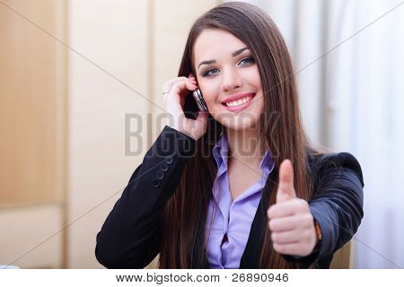 Happy successful businesswoman with cell phone and thumbs up gesture