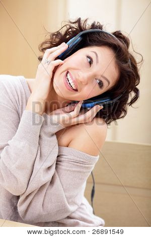 happy cute young lady listening to music on a headset
