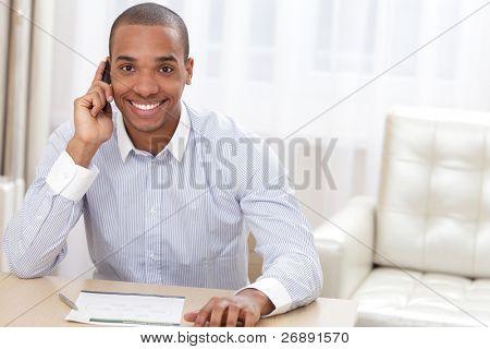 Joven empresario sonriente llamando en el teléfono