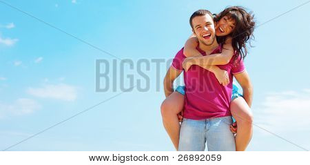 Happy young couple in casual cloths with a sky on background. Copyspace.