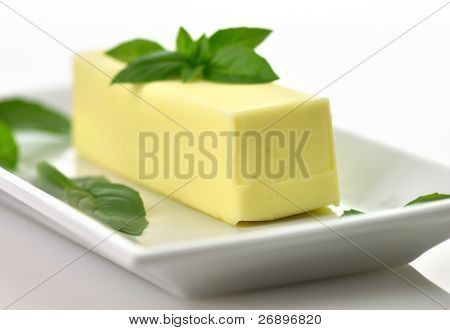 Fresh Butter stick on a white dish with basil leaves,close up