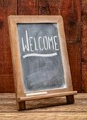 Welcome sign - white chalk handwriting on a blackboard against rustic barn wood poster