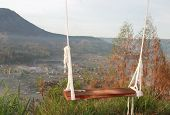 A Single Swing With Morning Mountain Panorama In Dreamy Mood. Mount And Local Home Residence As Back poster