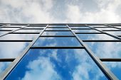 image of building exterior  - Reflection of a cloudy sky in glass wall of an office building - JPG