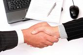 man and woman shaking hands in front of laptop and signed contract
