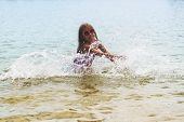 Happy Little Girl Playing In Shallow Water Waves.little Girl Playing In The Sea Waves, Girl Having F poster
