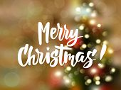 Merry Christmas Text, Hand Drawn Lettering.  Blurred Background With Christmas Tree And Glowing Ligh poster