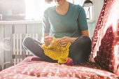 Woman Knits Crochet. The Girl Sits On The Couch And Knits From Knitting Yarn. Crochet Thick Threads. poster