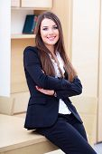 Young happy businesswoman in suit standing near the table in the office