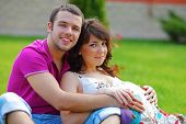 stock photo of pregnant woman  - Happy beautiful pregnant woman with his husband sitting on the lawn outside - JPG