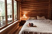 Rustic interior of log cabin bedroom. Cozy bed by big window. Breakfast on a tray in hotel. poster