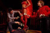 foto of bachelor party  - View of three men offering money to a stripper on stage - JPG