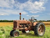 stock photo of tractor  - red old rusty tractor in a field - JPG