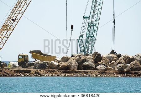 Building A Dike. Cranes And Excavator Put Stones