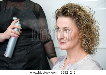Hairdresser Fixing Woman Hair With Hairspray