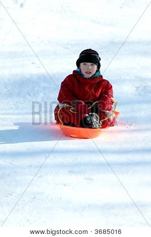 Boy In Red In Sled Going Downhill
